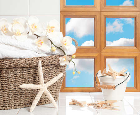 Basket of fresh laundry with clothespins against a blue sky window  photo