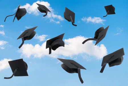 Graduation mortar boards thrown into a blue sky Banque d'images
