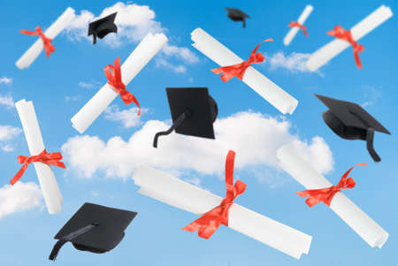 Graduation caps and diploma scrolls against a blue sky Stock Photo