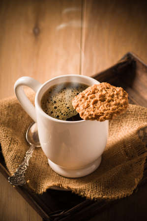 Cup of steaming coffee with biscuit on wooden tray