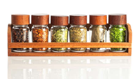 Jars of herbs and spices in wooden rack on white background
