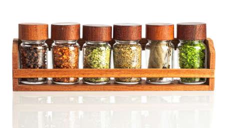 dried spice: Los frascos de hierbas y especias en bastidor de madera sobre fondo blanco Foto de archivo