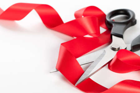 Cutting red ribbon with scissors on a white background photo
