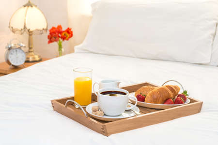 Breakfast served in bed on wooden tray with coffee and croissants