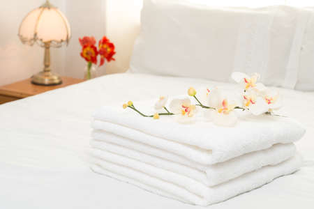 Freshly laundered white fluffy towels in bedroom interior photo