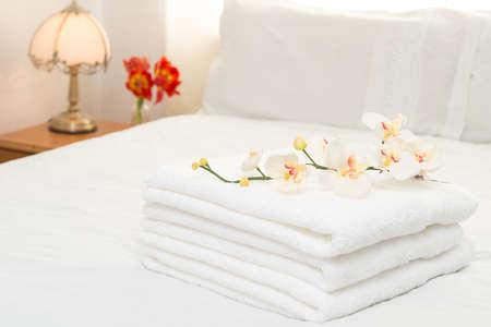 Fris gewassen witte pluizige handdoeken in de slaapkamer interieur Stockfoto