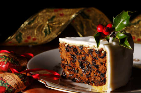 christmas food: Slice of Christmas cake decorated with holly and berries