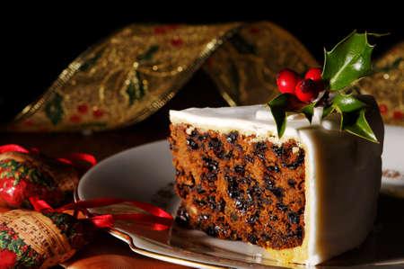 weihnachtskuchen: Slice of Weihnachtskuchen mit Stechpalme und Beeren dekoriert Lizenzfreie Bilder