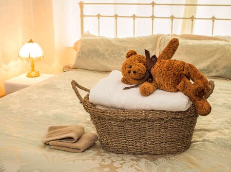 A basket of laundered towels with teddy bear on top, set in a bedroom. photo