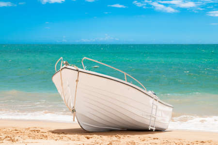 beached: Fishing boat on a sandy beach with blue ocean and summer sky Stock Photo
