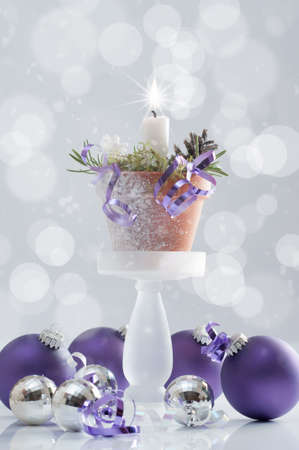 Christmas candle with purple bauble decorations photo