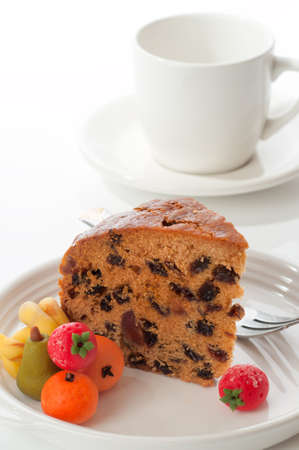 comfits: Slice of Dundee cake with marzipan fruits on a white background Stock Photo