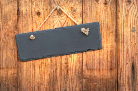 Blank slate sign hanging on a rustic wooden background Stock Photo - 14007968