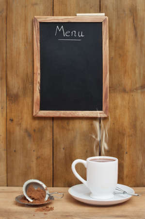 Hot chocolate against menu board in rustic setting photo