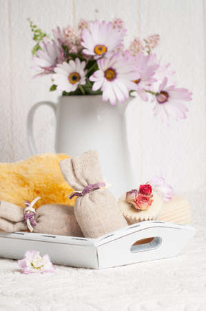 Bathroom soaps and sponge on tray and vase of flowers with vintage textured background photo