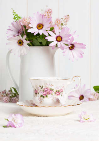 high tea: Floral teacup with jug filled with flowers