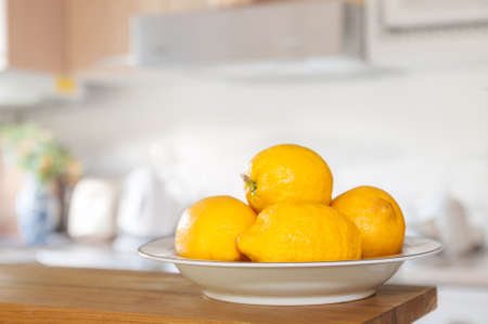 Fresh lemons in bowl sitting on countertop of kitchen, selective focus on front lemon with shallow dof