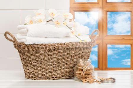lavander�a: Cesta de toallas reci�n lavadas en ventana de la cocina iluminada por el sol Foto de archivo