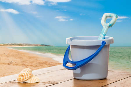 Holiday concept with bucket and spade against summer beach background photo