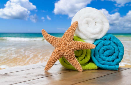 Summer beach towels with starfish against ocean background