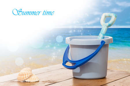 Bucket and spade with seashells against ocean background photo