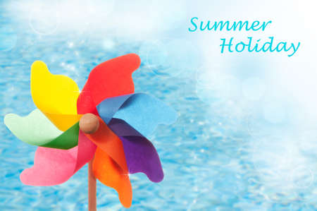 Summer holiday concept with windmill against blue background photo
