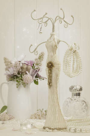 costume jewelry: Jewellery holder with bracelet and pearl necklace with antique scent bottle in background