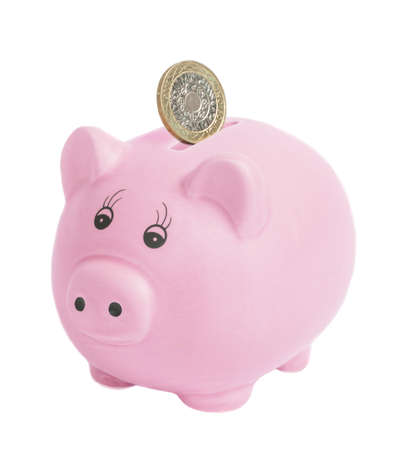 budget crisis: British two pound coin being inserted into piggy bank - isolated on a white bank background