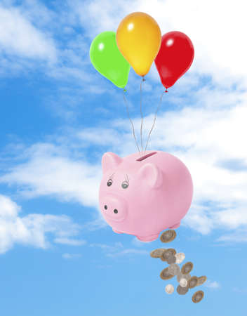 Piggy bank floating in sky losing money - financial crisis concept Foto de archivo