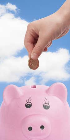 Pink pig money box with hand depositing British pound coin