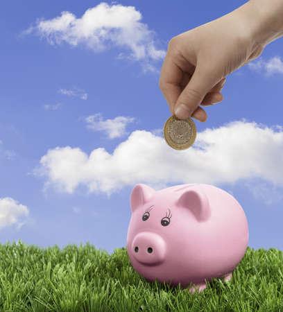 Hand depositing coin into piggy bank