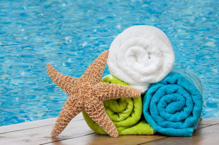 Colourful towels with starfish against sparkling swimming pool photo
