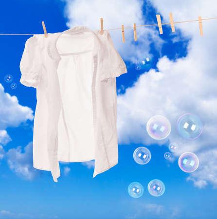 lavando ropa: Camisa blanca que cuelga en línea de lavado con burbujas de jabón contra un cielo azul Foto de archivo