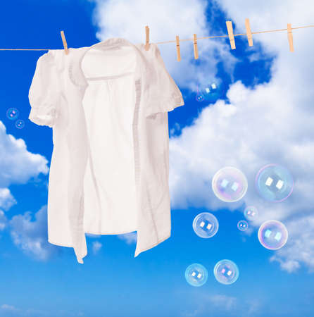 white clothes: White shirt hanging on washing line with soap bubbles against a blue sky