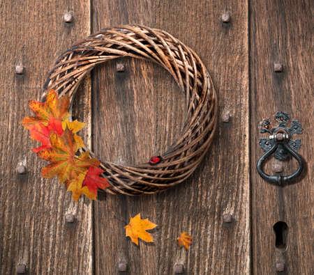 Autumn wreath hanging on heavy Gothic wooden door photo