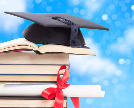 mortar board: Graduation concept with mortar board and diploma against a blue background