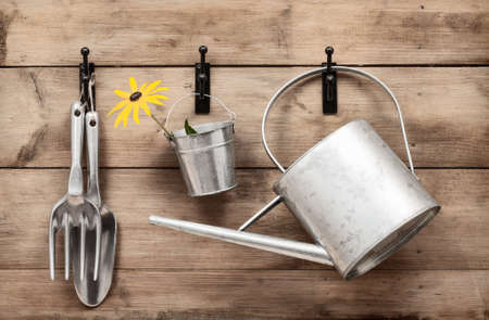 Garden tools hanging and watering can on shed door with vintage feel