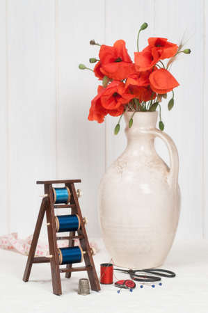 Sewing table with cotton spools and vase of poppies photo
