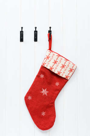 stockings: Christmas stocking hanging on the back of white wooden door Stock Photo