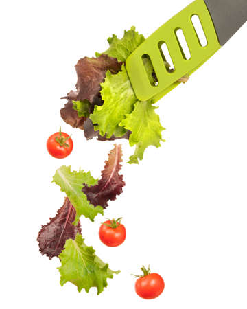 Lettuce leaves in salad tongs with falling tomatoes