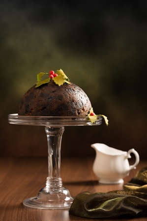 Christmas pudding decorated with holly and berries with festive background