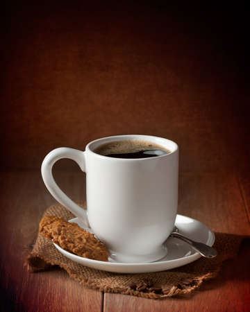 Cup of coffee with biscuits on burlap mat Stock Photo - 17331885