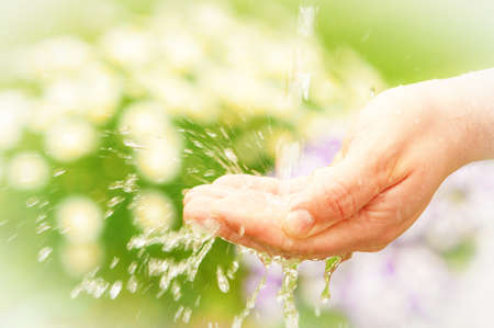 hand water: Water splashing through hand in summer garden with vintage feel Stock Photo