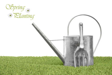 agricultural implements: Spring planting time with watering can and garden fork on grass with white isolated background Stock Photo