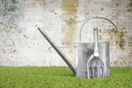 regar las plantas: Regadera y tenedor jardín contra una pared sucia