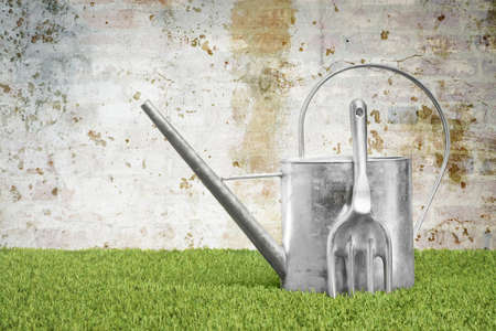 agricultural tools: Watering can and garden fork against a grungy wall