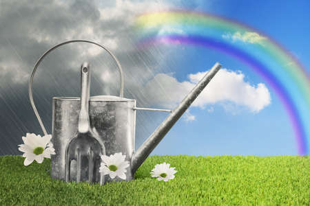 agricultural implements: Watering can against a rainy sky turning to blue with a rainbow