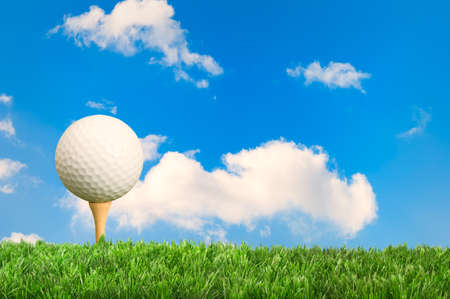Golf ball on tee with blue sky background photo