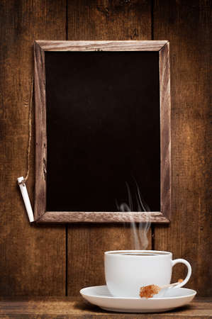Cup of steaming coffee against menu board