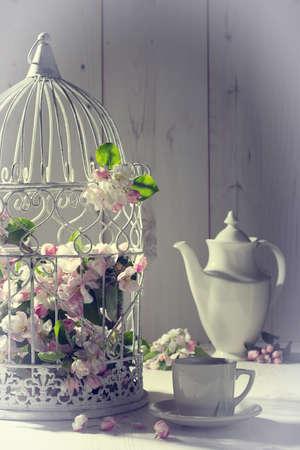minable: Th� vintage avec cage remplie de fleurs de printemps Banque d'images